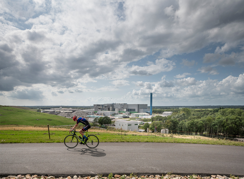Een wielrenner raast over de groene heuvels waar zich voorheen stortplaats de Blinkerd bevond.