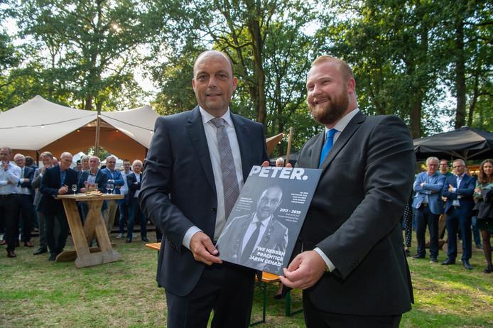 Wethouder Martijn Breukelman overhandigt Peter Snijders (links) een eigen glossy magazine.