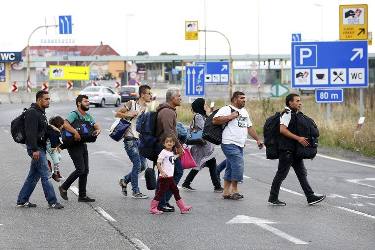 Vluchtelingen lopen bij de Hongaars-Oostenrijkse grensovergang nabij Nickelsdorf. Beeld reuters