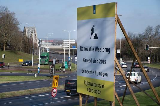 Het bord 'Renovatie Waalbrug Gereed eind 2019' op het Traianusplein in Nijmegen staat er al maanden. Maar het werk moet nog beginnen, de renovatie van de brug gaat anderhalf jaar duren.