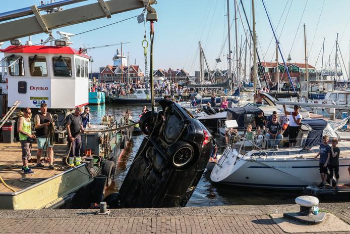 Een boot takelt de auto weer op de kade op Urk.