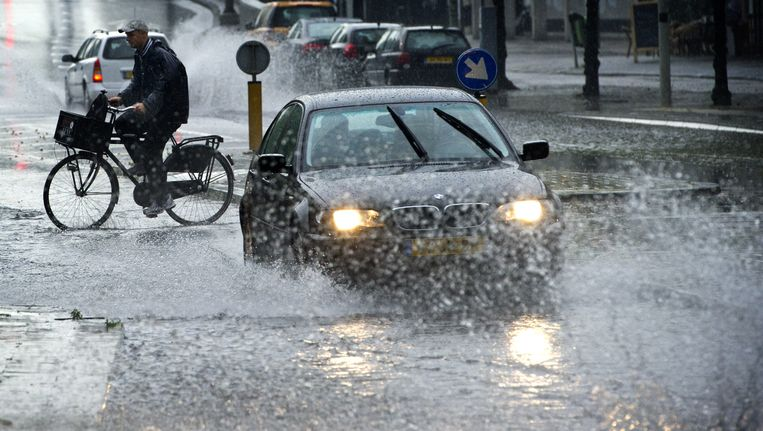 Auto's door de regen in de binnenstad van Amsterdam. Beeld anp
