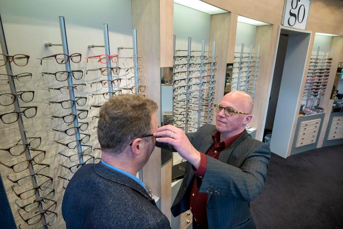 Peter van der Eijk helpt een klant in zijn optiekzaak in winkelcentrum Rijkerswoerd.
