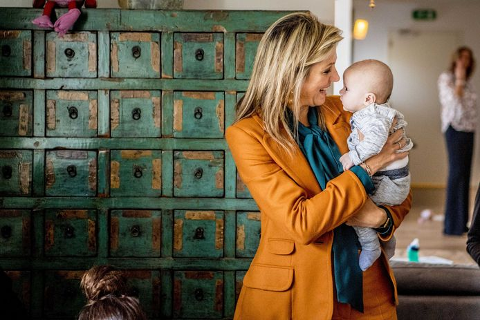 Koningin Máxima geniet zichtbaar van de baby op haar arm.
