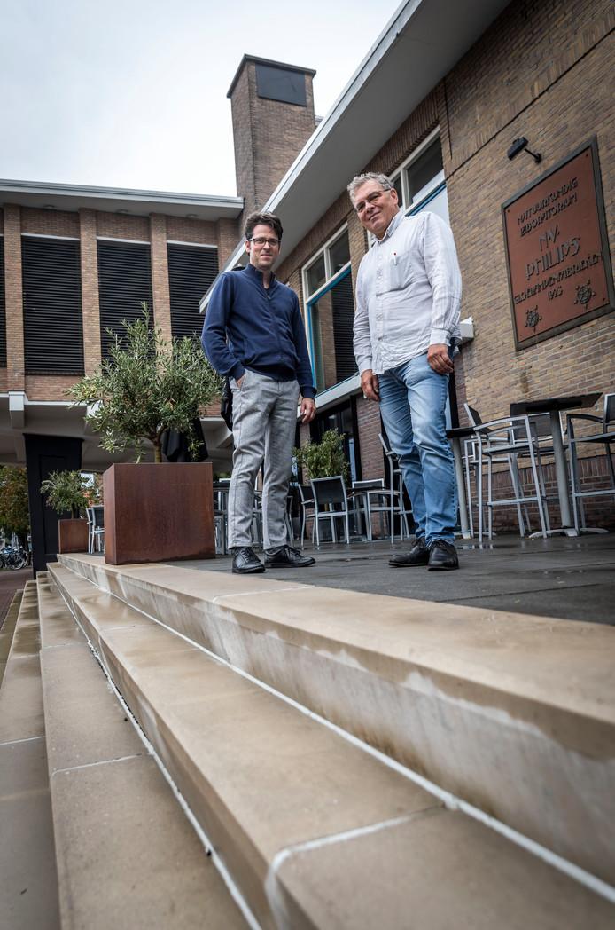 Paul Groenendijk (r) en Piet Vollaard (niet op foto) schreven architectuurgids over Eindhoven. René Erven (l) was hen behulpzaam. Hier staan ze bij Natlab, dat ook in het boek staat.