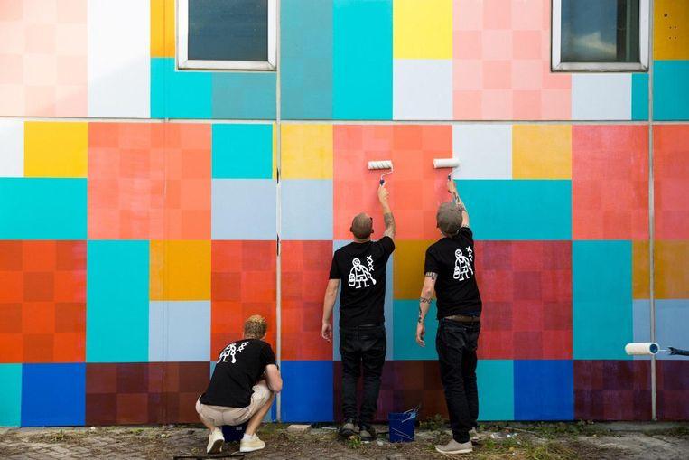 In samenwerking met azc-bewoners wordt de buitenkant van de bajes van een vrolijk likje verf voorzien. Beeld Favela Painting