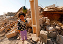 Een Iraans meisje op de puinhopen van haar huis na een zware aardbeving in de provincie Kermanshah bij de grens met Irak in november 2015. Honderden mensen kwamen daarbij om het leven, duizenden raakten dakloos.