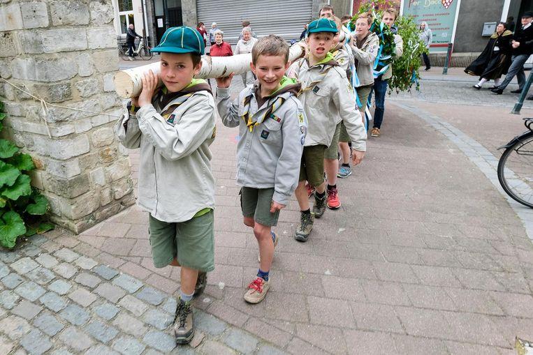 Enkele jonge welpjesscouts dragen de meiboom door het centrum.