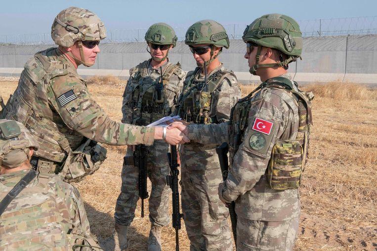 Een Amerikaan schudt een Turkse militair de hand in Noord-Syrië bij een gezamenlijke patrouille door het gebied. Beeld EPA