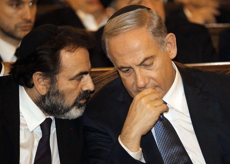 De Israëlische premier Benjamin Netanyahu (R) gisteravond in de Grote Synagoge van Parijs. Beeld null