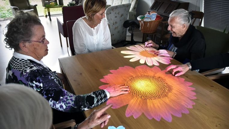 Ouderen aan een 'Tovertafel': een lichtspel voor mensen met ernstige dementie. Beeld Marcel van den Bergh