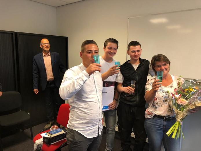 Martin Weijermans, Nick van Cadzand en Manuel Drechsler  (vlnr) hebben hun diploma en proosten met Astrid van Kleeff op de een nieuwe toekomst. Docent Peter Moll kijkt op de achtergrond toe.