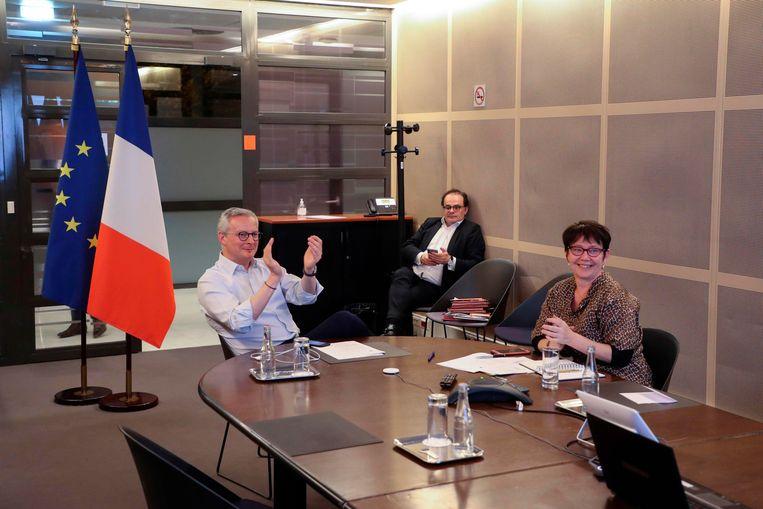 De Franse minister van Financiën Bruno Le Maire (links) klapt in zijn handen als er tijdens de Europese videotop een akkoord is bereikt over een noodpakket van ruim 500 miljard euro om de financiële gevolgen van de coronacrisis te bestrijden.   Beeld Foto Ludovic Marin / AFP