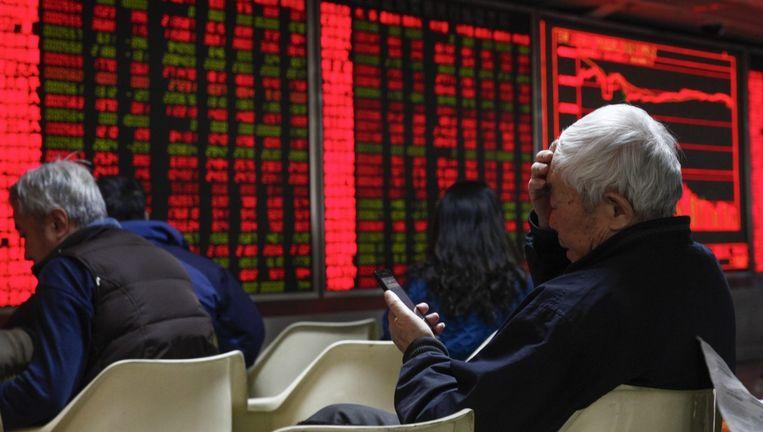 De koersborden in China kleurden gisteren rood en de beurshandel werd stilgelegd. Vandaag herstelden de effectenbeurzen in China en elders zich enigszins. Beeld Epa