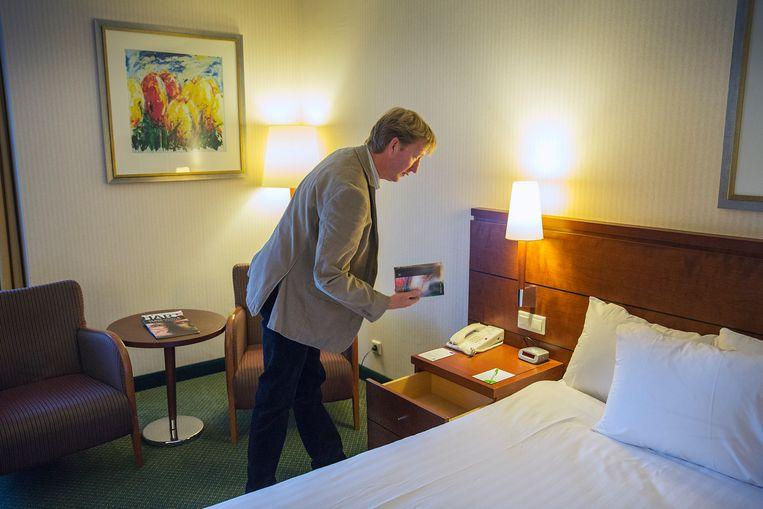 Henk Kamminga van de Bijbelvereniging controleert of er nog een bijbel ligt in een hotel in Hoofddorp. Beeld Werry Crone