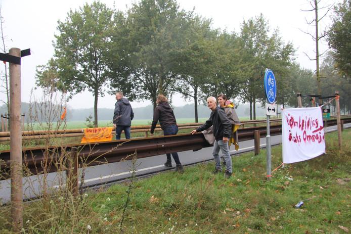 Wandelaars klimmen over de vangrail langs de Rijksweg bij Reek, zoals afgelopen zaterdag bij de opening van de Reekse Ommetjes.