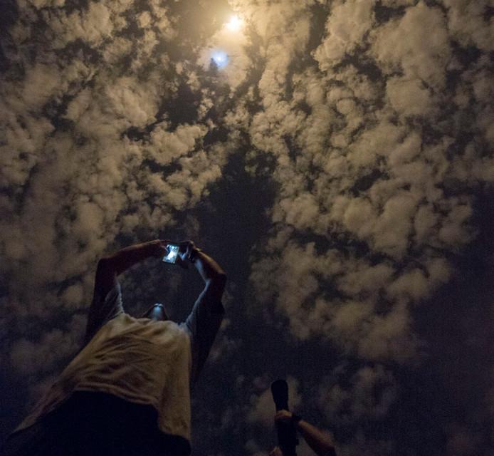 Toeschouwers fotograferen een Ariane-5 raket die met satellieten aan boord opstijgt vanaf het NASA-lanceerplatform in Frans Guyana. Foto S. Martin