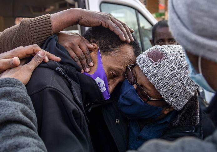 Vader Bayle Gelle (links) wordt getroost tijdens een demonstratie zondag.