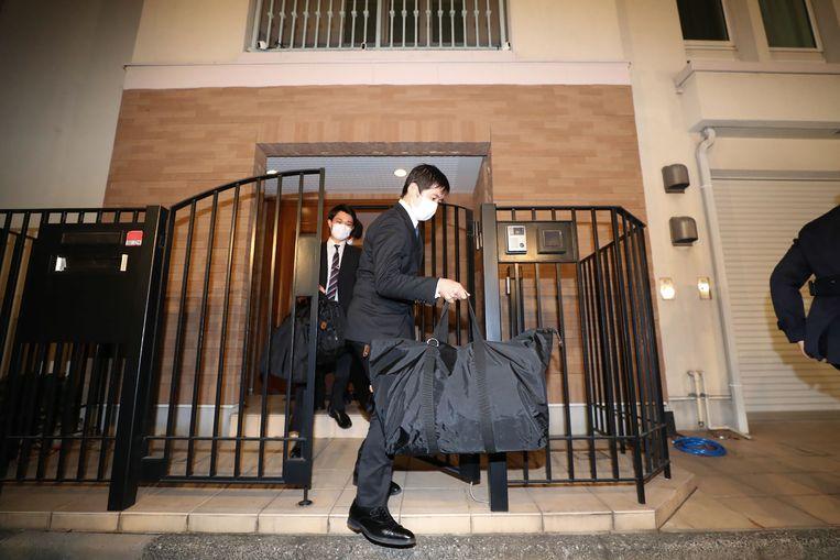 Een Japanse aanklager verlaat het huis van Carlos Ghosn met een zwarte weekendtas. Beeld AFP