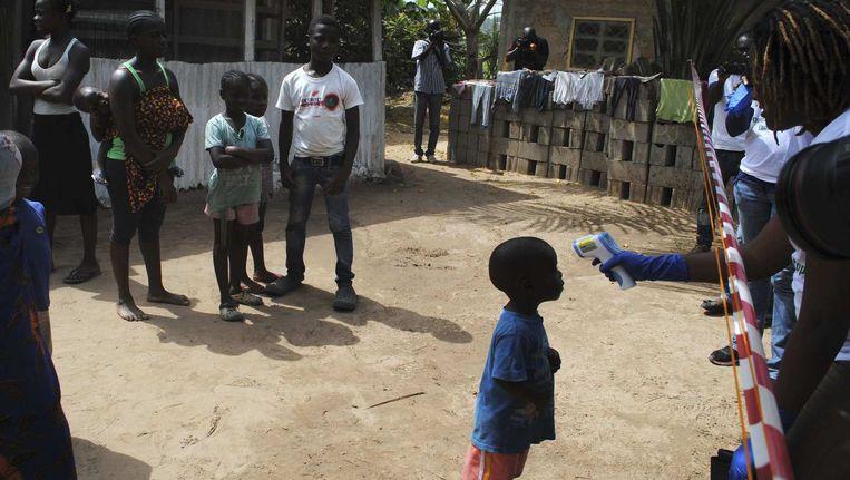 De temperatuur van een jongen die in contact is geweest met een vrouw die ebola had wordt opgenomen in Monrovia, Liberia. Beeld reuters