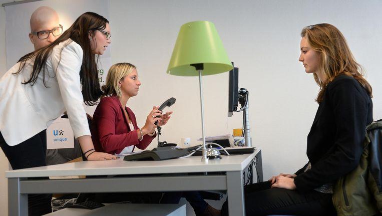 Werkzoekende (r) bij uitzendbureau Unique. Links twee medewerkers die iets op de computer zoeken (archiefbeeld). Beeld null