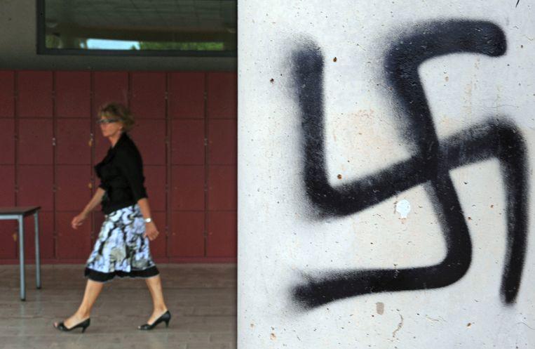 Een leraar loopt langs een swastika die op een muur bij een school in Agde, Zuid-Frankrijk, is gespoten. Beeld AFP
