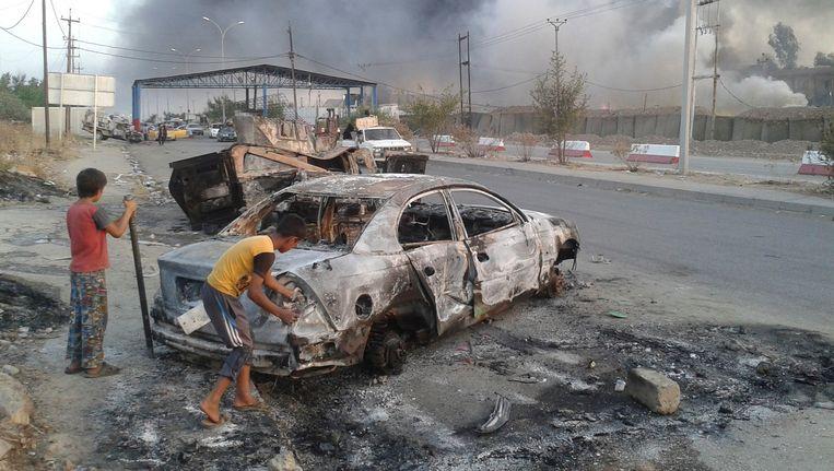Kinderen staan naast een uitgebrande auto in Mosul, de noordelijke Iraakse stad die in handen is gevallen van ISIS. Beeld null