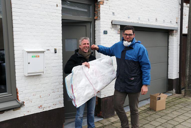 IOK-medewerker Stijn Ruymaekers overhandigt een plaatzak aan bewoner Jiri Van Peer.