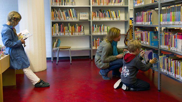 Moeder en kind op zoek naar een boek in de bibliotheek, een voorziening die ook door burgers zelf gerund kan worden. Beeld ANP