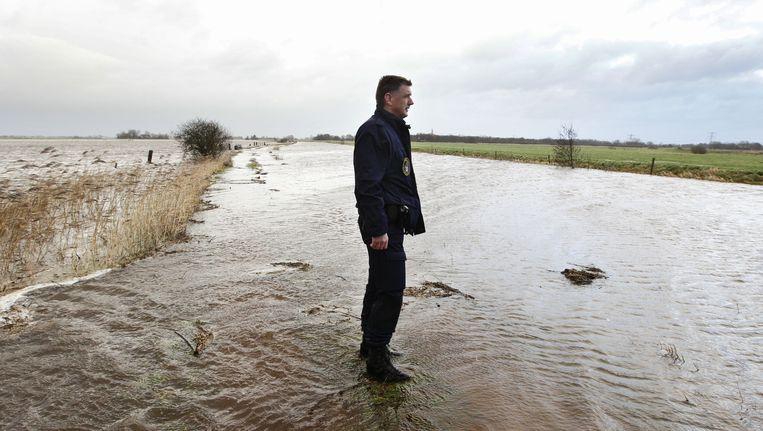 Een politieagent staat in de Groningse plaats Tolbert in het water dat over de dijk de weilanden in loopt, 5 januari 2012. Beeld null
