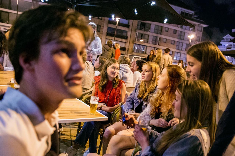 Nederlandse jongeren op een terras op het Alfred Verweeplein in Knokke-Heist. Beeld Arie Kievit