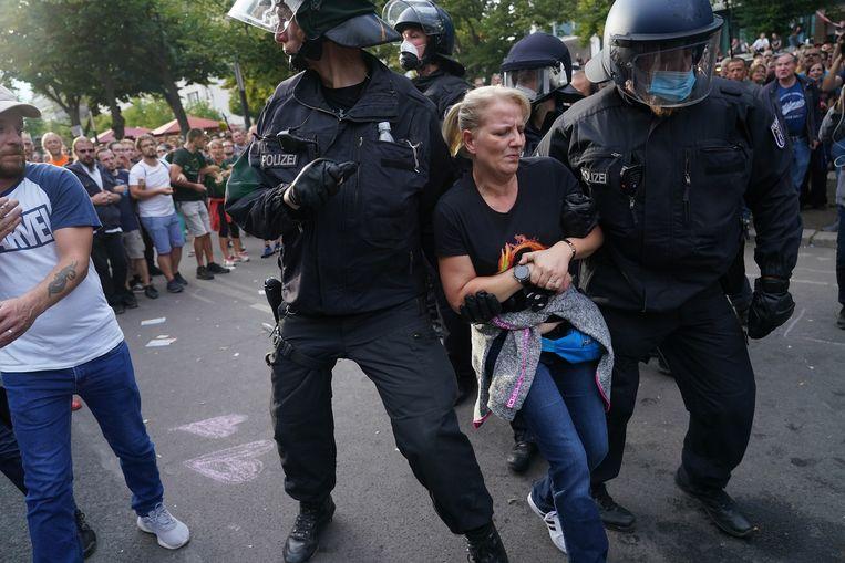 Op Unter den Linden wordt een vrouw in een QAnon-shirt afgevoerd. Beeld Getty Images