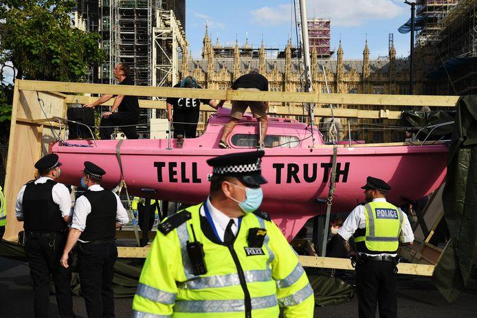 Betoger reden een voertuig met daarop een roze boot het parlementsterrein op.