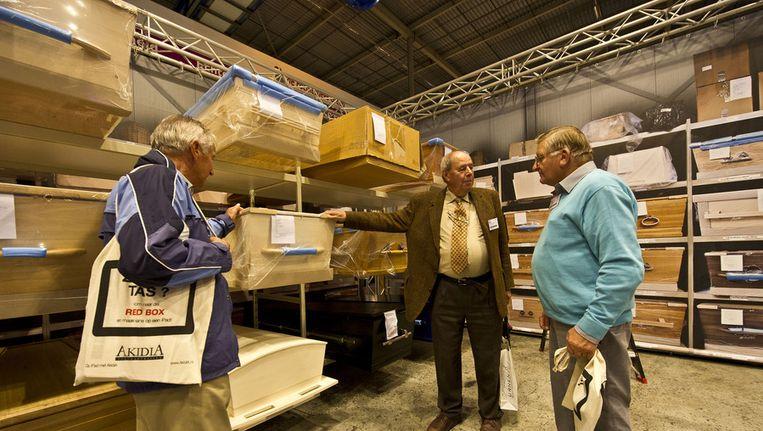 Begraafplaatsbeheerders keuren tijdens de Uitvaart Vakbeurs 2012 enkele lijkkisten. Beeld ANP