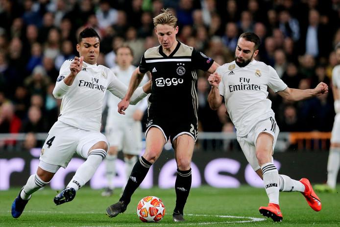 Frenkie de Jong in duel met Dani Carvajal (r) en Casemiro (l). Vanwege de wedstrijd in Madrid werd het competitieduel met PEC Zwolle verschoven naar vandaag.