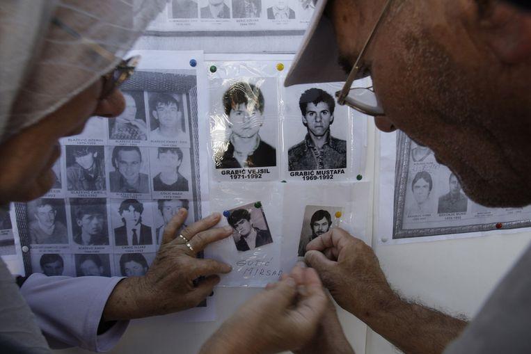 Bosnische moslims bevestigen foto's van vermoorde familieleden aan een herdernkingsmuur in Sarajevo. Beeld ap