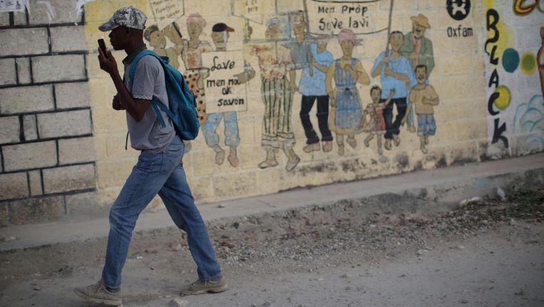 Een man loopt langs een schildering van Oxfam in Corail, waar veel mensen een onderkomen moesten vinden na de aardbeving van 2010 in Haiti. Beeld null