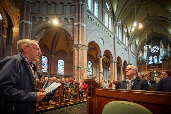 Harrie van Schijndel vertelt over de Petruskerk, met gedeputeerde Erik van Merrienboer vooraan in de kerkbanken (met sjaal).