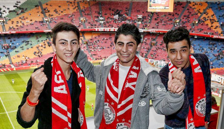 Shant, Hagop en Mohammed in de Arena tijdens een wedstrijd van Ajax. Beeld Pro Shots / Stanley Gontha