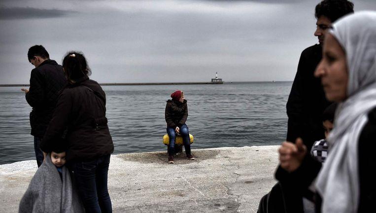 Een vrouw zit op een dukdalf in de haven van Lesbos. Beeld afp