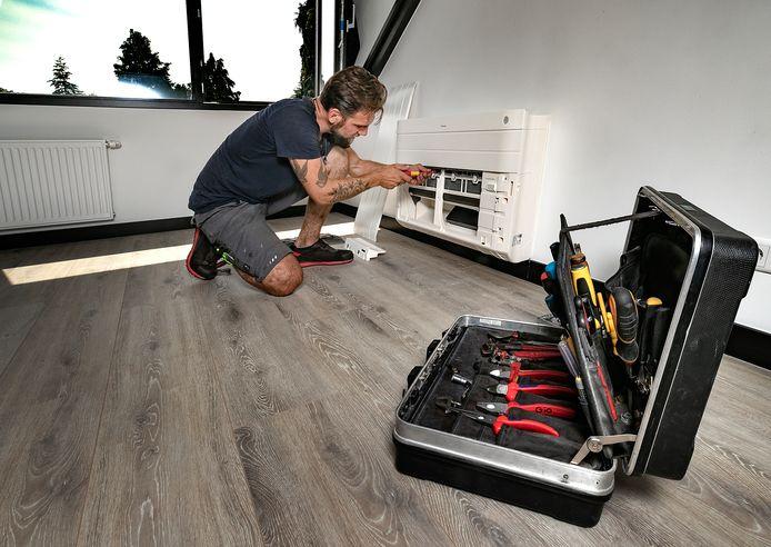 Giovanni Esman monteert de airco op een hete zolder in Geldrop.