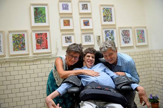 Andrei Fokkink, met links zijn tekenmentor Gerdie Schiphorst en rechts zijn vader Arie.  Aan de wand hangt werk van Andrei, dat te koop is voor het goede doel.