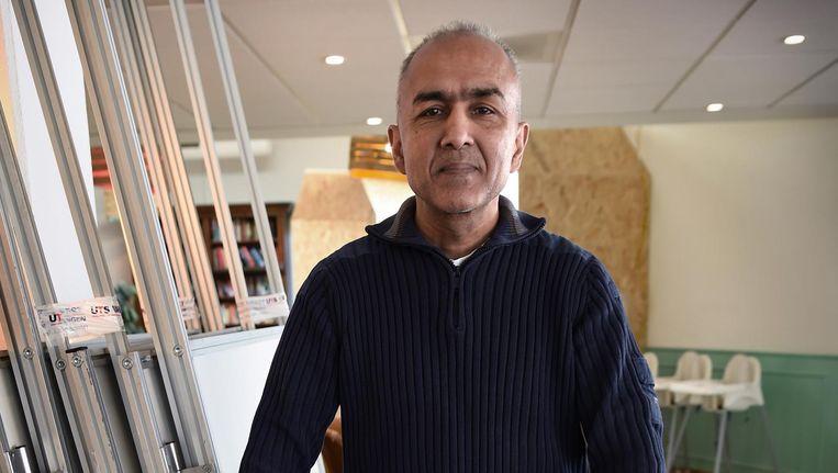 Radjen Somai in 'zijn' stemlokaal in opbouw. Beeld Marcel van den Bergh / de Volkskrant