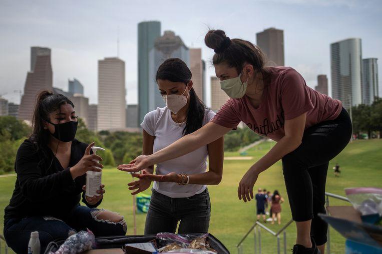 Vrouwen delen handsaniter in Houston, Texas.