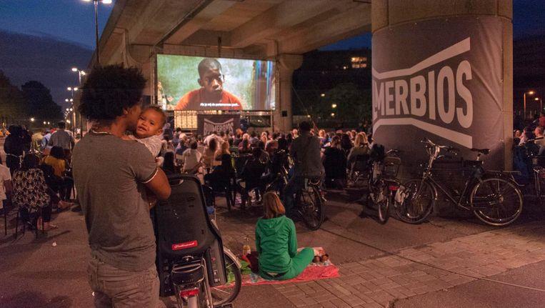 Terwijl de metro bovenlangs dendert, toont de Bijlmerbios films in de buitenlucht. Beeld Hans Mooren