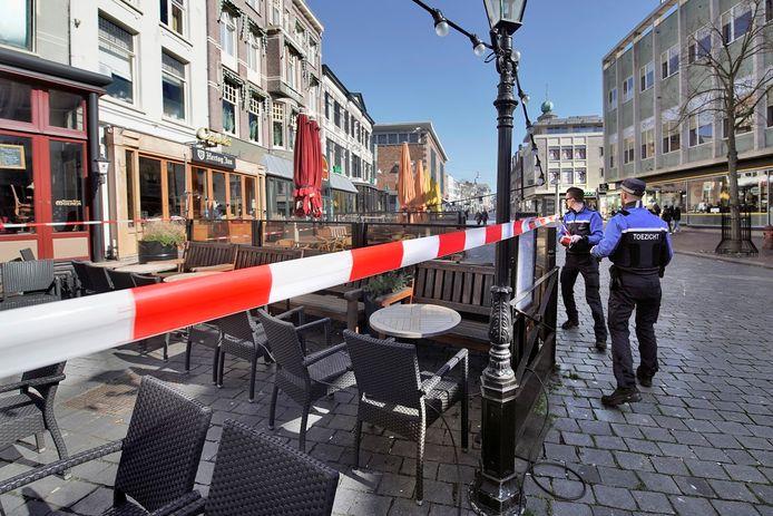 De Nijmeegse binnenstad tijdens de coronacrisis. Medewerkers van Bureau Toezicht spanden vorige week afzetlint voor de terrassen van gesloten horecagelegenheden.
