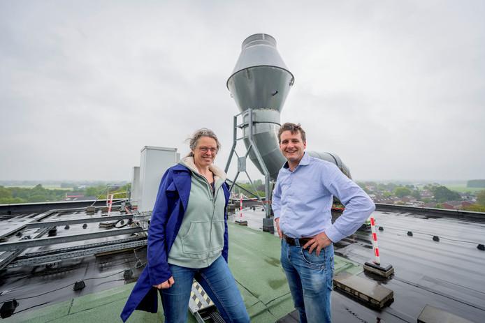 Voorzitter Jet Mars van de werkgroep Haarle Energie Neutraal en directeur Hans Verheul van de CAVV Zuid-Oost Salland op het dak van de fabriek met op de achtergrond de pijp die nu nog lucht uitstoot van zo'n 60 graden Celsius. Deze restwarmte kan mogelijk ook worden gebruikt voor het verwarmen van de sporthal en andere gebouwen in Haarle.