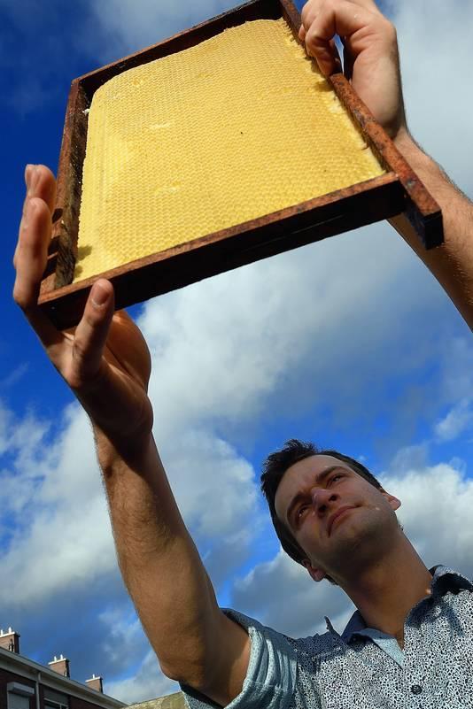 Johannes Leenders van het innovatieve bedrijf Johnny Bee Good werpt een  kritische blik op een honingraat uit een van zijn kasten.