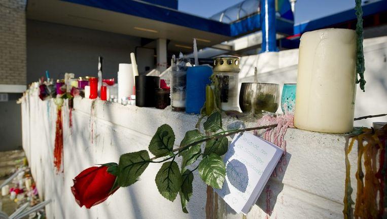 Bij de ingang van winkelcentrum De Ridderhof staan maandag kaarsen en bloemen. Beeld anp