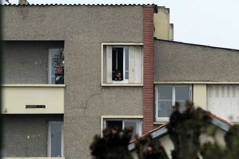 Een buurtbewoner kijkt uit het raam naar de belegering. Beeld reuters